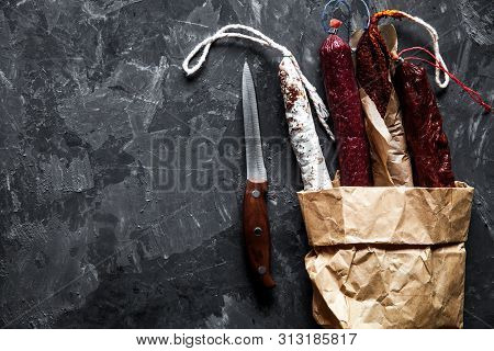 Sausages On A Paper Texture On A Dark Background With Pepper A