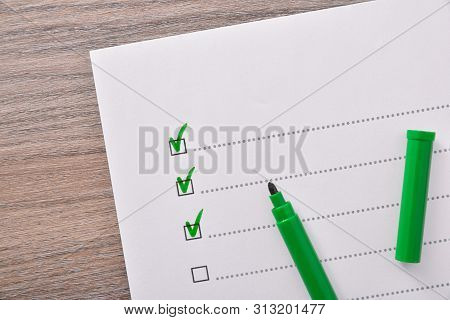 Questionnaire Concept With Several Options Validated With Green Marker Pen On Wooden Table. Horizont