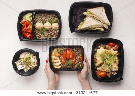 Healthy lunch. Tasty food in different boxes for day ration in woman hands poster