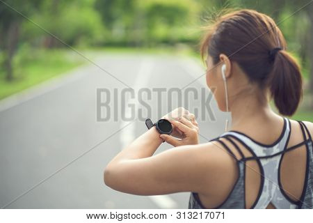 Woman Setting Up The Fitness Smart Watch For Running. Sportswoman Checking Watch Device. Young Fitne