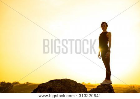 Young Woman Standing on the Rock Against a Hot Beautiful Summer Sunset. Adventure and Healthy Active Lifesyle Concept.