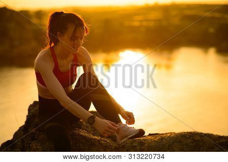 Young Sports Woman Tying Running Shoes and Preparing for Trail Run at Sunset. Healthy Lifestyle and Active Sport Concept.