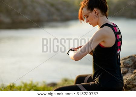Young Woman Runner Using Multisport Smartwatch at Sunset on the Mountain Trail. Closeup of Hands with Fitness Tracker. Training and Sports Concept.