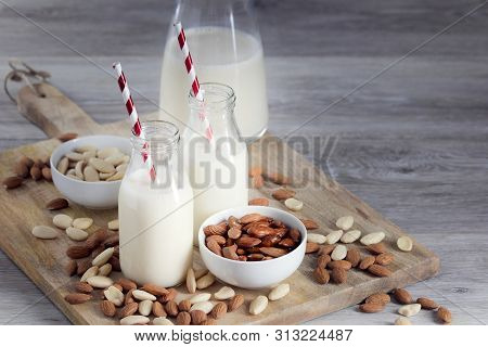 Wooden Table Top With Glasses And A Jug With Almond Milk, Almond Drink, Peeled And Unpeeled Almonds