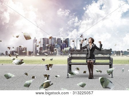 Young Woman With Megaphone Sitting On Wooden Bench. Money Income Concept. Female Motivational Speake