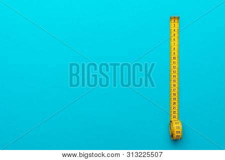 Top View Of Yellow Soft Measuring Tape. Minimalist Flat Lay Image Of Tape Measure With Metric Scale
