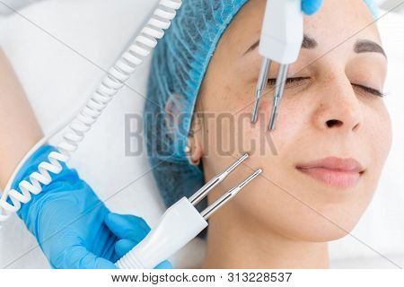 Beautician procedure of microcurrent therapy of the patient's face. A young girl is undergoing a course of spa treatments in the office of a beautician. Moisturizing, cleaning and facial skin care. Cosmetic procedures. poster