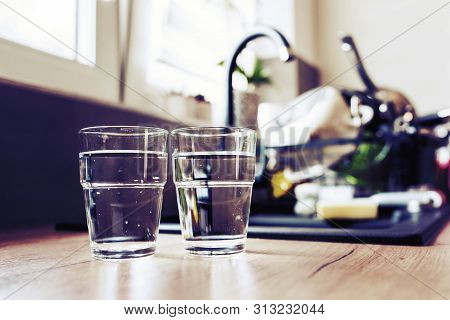 Two Glasses Of Water In Kitchen, With Tap Water And Two Bottles Of Mineral Water. Shallow Depth Of F