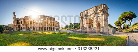 Panorama Of Colosseum And Constantine Arch At Sunrise In Rome, Italy, Europe.