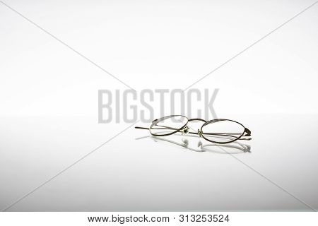 Golden Metallic Eyeglasses For Vision Issues Or Protection, Isolated On White Background With Reflex