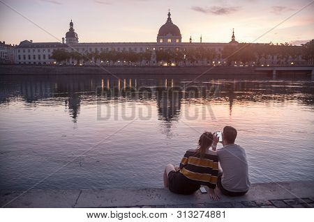 Lyon, France - July 18, 2019: Couple, Lovers, Looking At A Smarthone On The Riverbank Of The Rhone,
