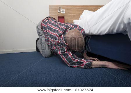 Man looking under bed