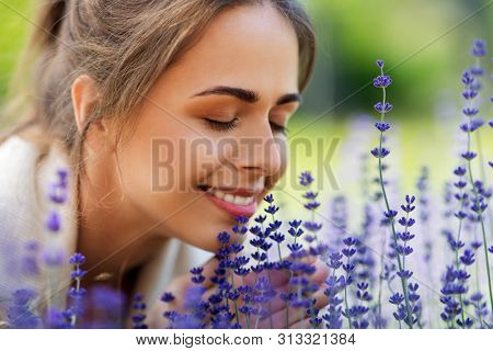 gardening and people concept - close up of happy young woman smelling lavender flowers at summer garden