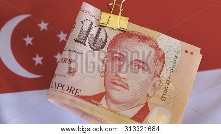Bundle Of Singaporean Dollars With The Singaporean Flag.