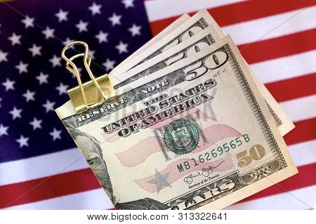 American Fifty Dollar Notes On A Clip With The American Flag.