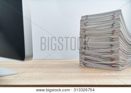 Stack Of Overload Paperwork Report And Computer On Wooden Table