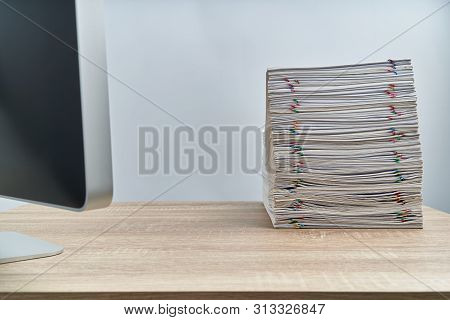 Pile Of Overload Paperwork Report And Computer On Wooden Table