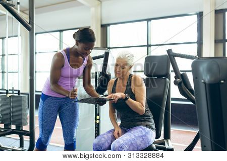 Front view of fit young African-american female trainer discussing over clipboard with active senior Caucasian woman in fitness studio. Bright modern gym with fit healthy people working out and