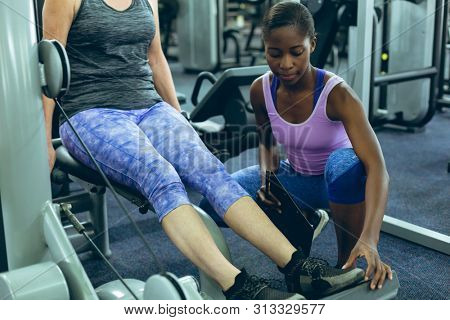 Front view of young fit African-american female trainer assisting active senior Caucasian woman to work out on leg curl machine in fitness center. Bright modern gym with fit healthy people working out