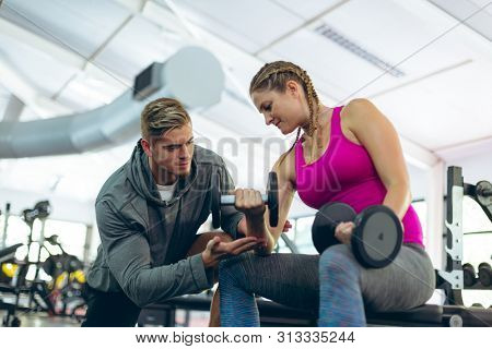 Low angle view of handsome young Caucasian male trainer assisting fit young Caucasian female athlete to exercise with dumbbells in fitness center. Bright modern gym with fit healthy people working out