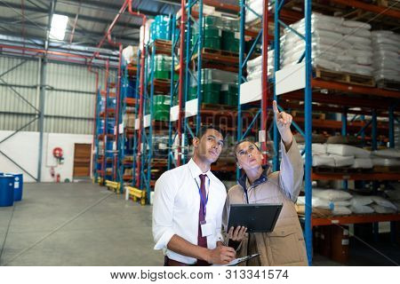 Front view of Caucasian warehouse staffs discussing over digital tablet in warehouse. This is a freight transportation and distribution warehouse. Industrial and industrial workers concept