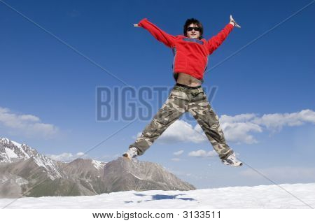 Teenager In Red Sport Pullover Jumping Over Blue Sky, Tien Shan