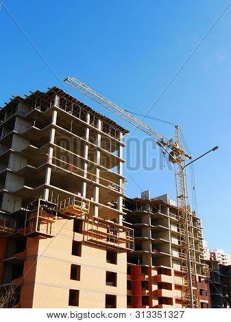 Concrete Building Under Construction. Construction Site. Construction Crane Near Building.