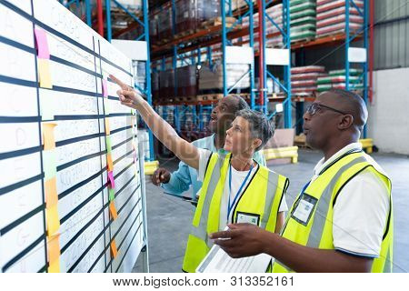 Side view of mature diverse warehouse staffs discussing over whiteboard in warehouse. This is a freight transportation and distribution warehouse. Industrial and industrial workers concept
