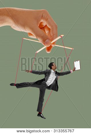 Man Like A Puppet In Somebodies Hands On Green Background. Concept Of Unfair Manipulation, Phycology