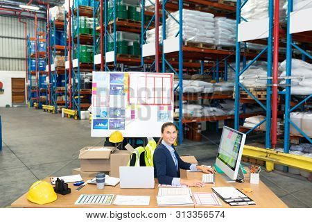 Portrait of beautiful Caucasian female manager working on computer at desk in warehouse. This is a freight transportation and distribution warehouse. Industrial and industrial workers concept
