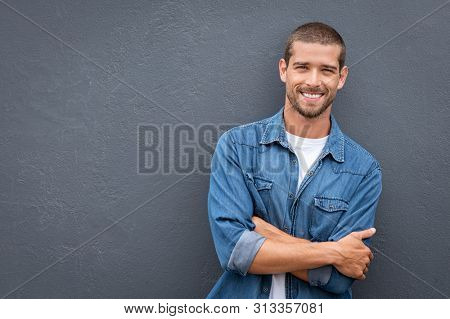 Portrait of smiling young man in casual denim shirt keeping arms crossed and smiling while standing against grey background. Stylish and confident guy leaning against gray wall with copy space.