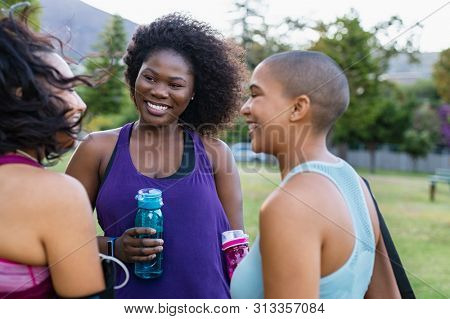 Smiling curvy girls in group chatting. Three friends talking after sporty exercising outdoor. Group of active multiethnic young women talking to each other after fitness workout at park.