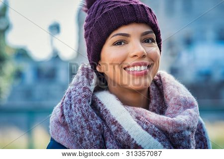 Closeup face of a young happy african woman enjoying winter wearing scarf and cap. Smiling brazilian girl looking at camera in a cold day. Multiethnic woman with knitted bordeaux hat and woolen scarf.