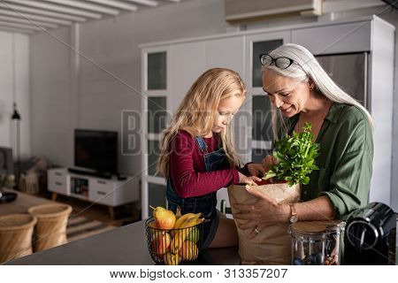 Grandmother and her granddaughter holding grocery shopping bag with vegetables at home. Happy old grandma holding paper bag with vegetables while grandchild removing food from bag.