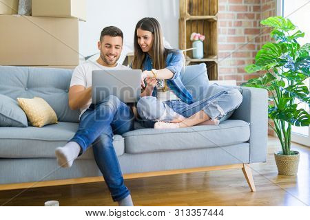 Young couple moving to a new home relaxing sitting on the sofa using computer laptop, smiling happy for moving to new apartment