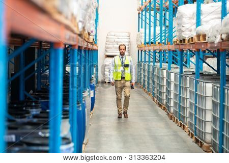 Front view of Caucasian male supervisor walking in aisle of warehouse. This is a freight transportation and distribution warehouse. Industrial and industrial workers concept poster