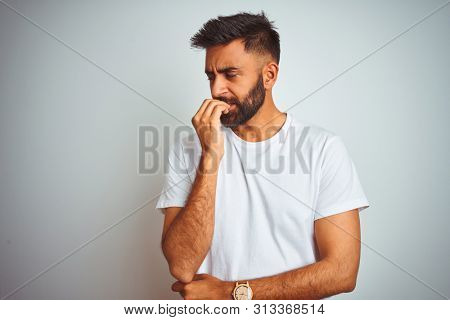 Young indian man wearing t-shirt standing over isolated white background looking stressed and nervous with hands on mouth biting nails. Anxiety problem.