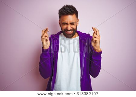 Young indian man wearing purple sweatshirt standing over isolated pink background gesturing finger crossed smiling with hope and eyes closed. Luck and superstitious concept.