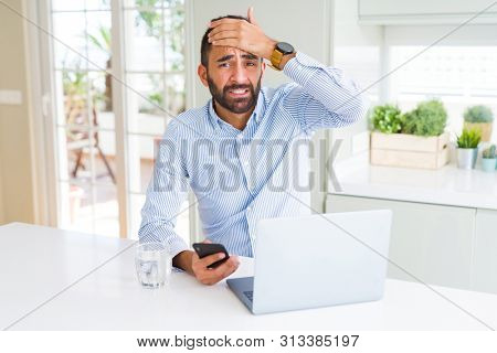 Handsome hispanic business man using laptop and smartphone stressed with hand on head, shocked with shame and surprise face, angry and frustrated. Fear and upset for mistake.