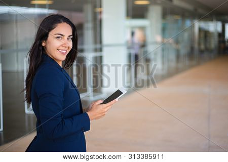 Happy Confident Professional Using Tablet In Office Hall. Young Latin Business Woman Holding Tablet