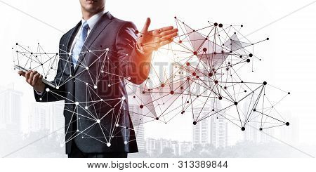 Businessman With Documents Pointing On Abstract Network With Polygonal Shapes. Standing Entrepreneur