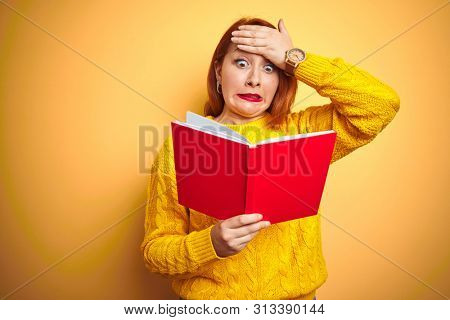 Young redhead teacher woman reading red book over yellow isolated background stressed with hand on head, shocked with shame and surprise face, angry and frustrated. Fear and upset for mistake.