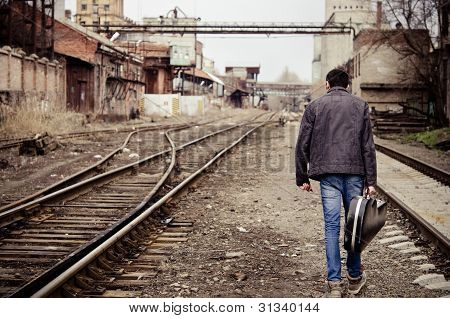 Young Man With Guitar Case Is Going Away Among Industrial Ruins