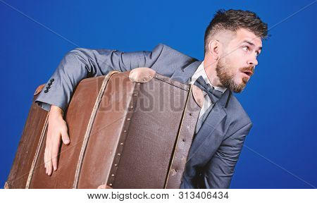 business trip with retro suitcase. heavy bag. mature traveller. stylish esthete with vintage bag. bearded man in formal suit. surprised businessman in bow tie. Complementing his style with bag poster