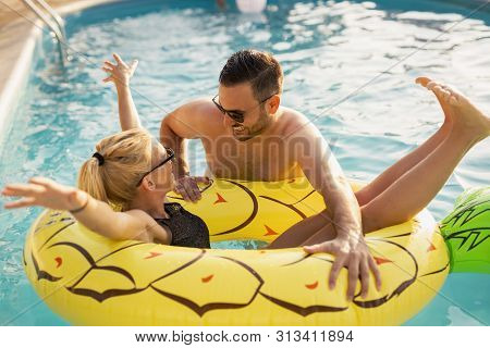 Couple In Love At A Poolside Summer Party, Sunbathing And Having Fun; Girl Floating In The Pool On A