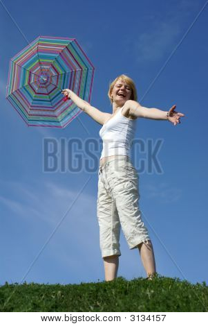 Young Charming Girl With Umbrella Against Blue Sky