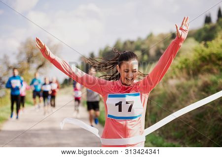 Young Woman Runner Crossing Finish Line In A Race Competition In Nature.