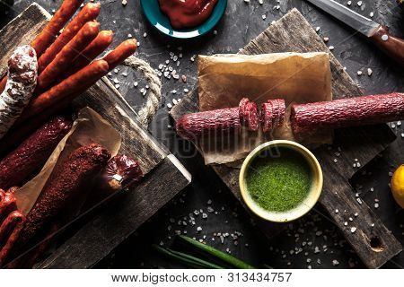 Sausage On A Dark Background With Elements Of Cooking. Cucumber, Onion, Ketchup