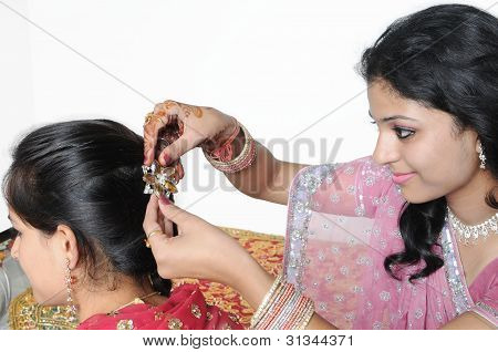 Indian Lady putting hair clip in other girl's hairs.