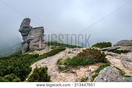 Summer Mountain Ridge With Big Vertical Stony Rocks. Clouds And Fog. Carpathian, Chornohora, Vuhatyj